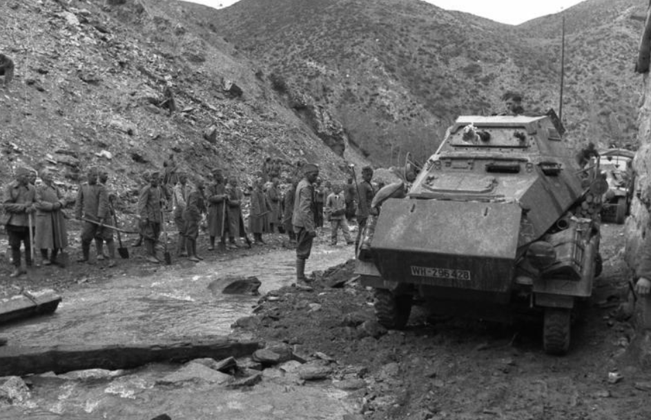 Yugoslav POWs supervised by Bulgarian soldiers with a German armored car